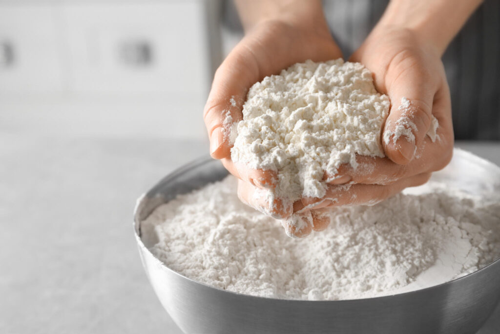 Woman holding gluten free flour above bowl on table