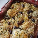 Kalamata and Lemon Chicken baked in a glass dish with a red towel underneath
