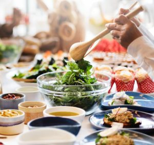Woman tossing a salad in glass bowl set on a table full of dishes and food