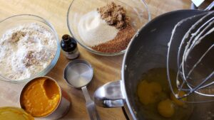 raw ingredients for the pumpkin bread in bowls and measuring cups