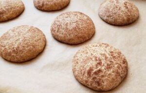 Freshly baked snickerdoodle cookies on a baking sheet lined with parchment paper