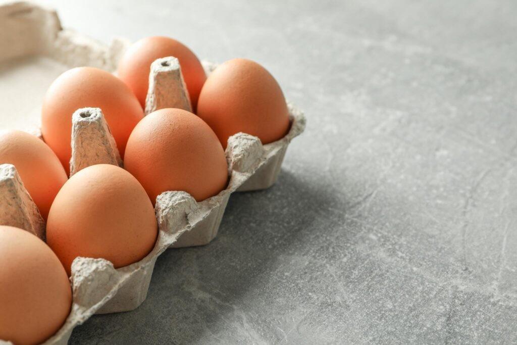 Brown eggs in carton on gray counter