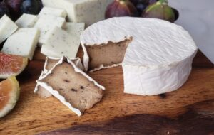 wheel of dairy free brie on a wooden board