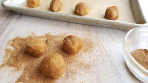 snickerdoodle dough balls rolled in cinnamon sugar on a white countertop