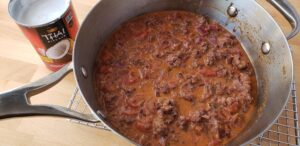 pan with red wine sausage sauce sitting next to an open can of coconut milk