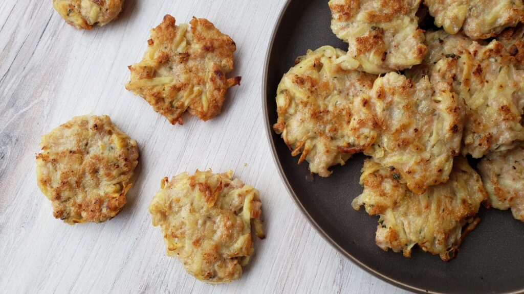 hashbrown fritters on a plate and spilling onto the counter