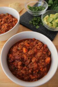 bowls of big batch chili recipe with beef crockpot